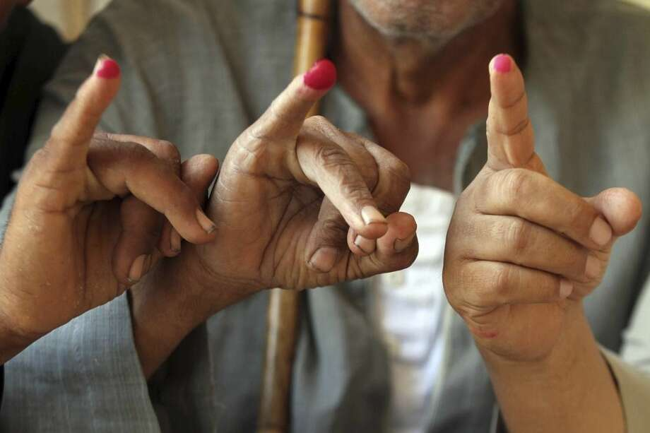 Voters display their his inked fingers after casting their ballots at a polling station during the first round of the parliamentary elections, in Giza, Cairo, Egypt, Sunday, Oct. 18, 2015. (AP Photo/Khaled Kamel)