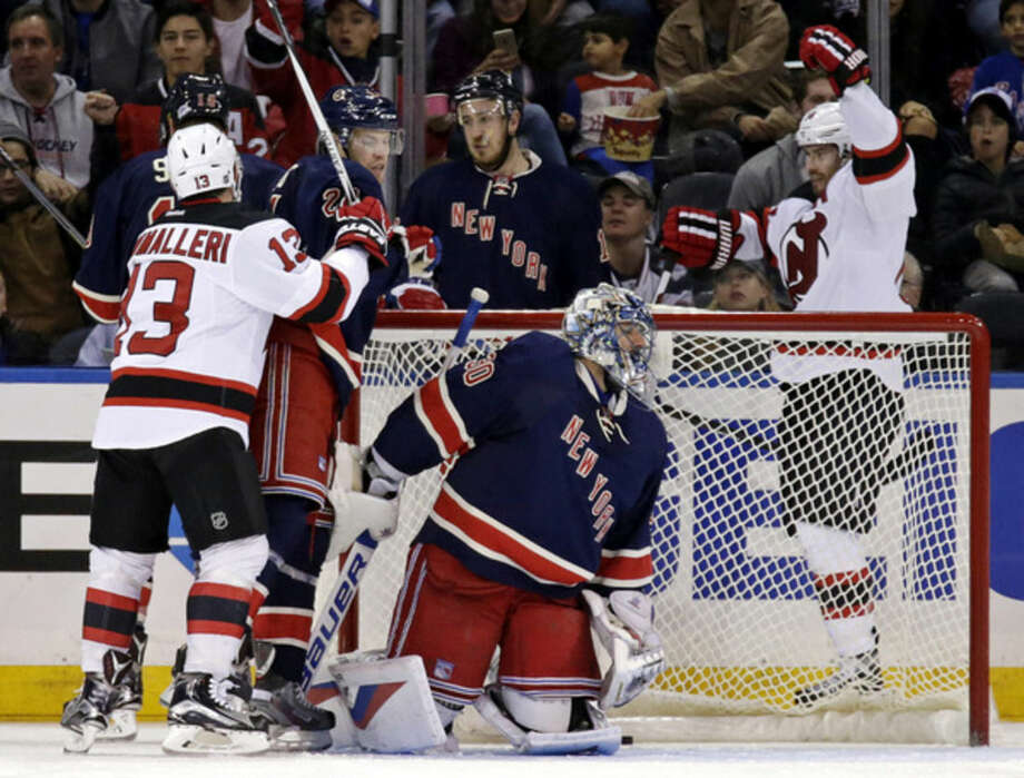 New Jersey Devils center Adam Henrique, right, celebrates after scoring a goal against New York Rangers goalie Henrik Lundqvist, of Sweden, during the second period of an NHL hockey game at Madison Square Garden on Sunday, Oct. 18, 2015, in New York. (AP Photo/Adam Hunger)