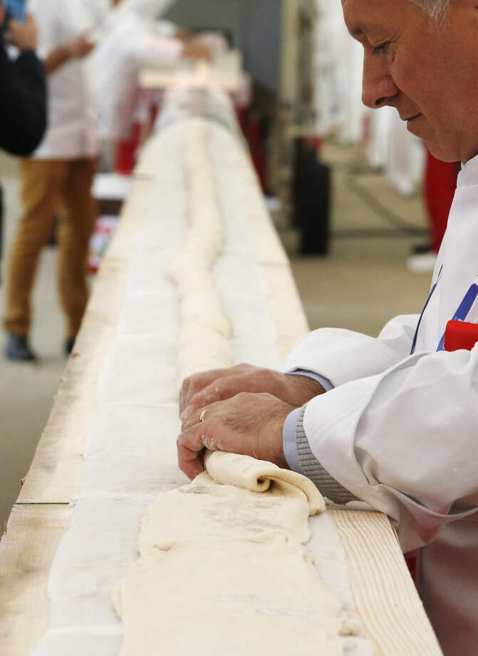 A baker prepares a record long baguette at the Expo 2015 world's fair, in Rho, near Milan, Italy, Sunday, Oct. 18, 2015. A judge from the Guinness World Record Judge has certified a 122-meter -long (400-foot-long) baguette baked at the Milan Expo 2015 World's Fair as the longest in the world. The Italian maker of Nutella, Ferrero, backed the enterprise to beat the 111-meter record held by a French supermarket chain. (AP Photo/Antonio Calanni)