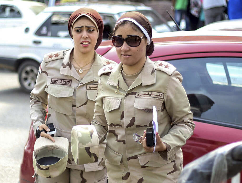 Female members of the armed forces arrive to work at a polling station during the first round of the parliamentary election, in Giza, Cairo, Egypt, Sunday, Oct. 18, 2015. (AP Photo/Samer Abdallah)