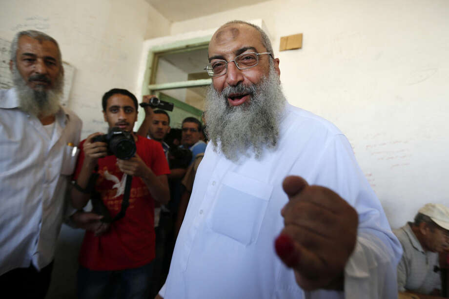The deputy head of Egypt's Al-Nour Party cleric Yasser el-Borhamy, shows his inked finger after he casts his vote during the first round of Egyptian parliamentary elections, at a polling station in Alexandria, Egypt, Sunday, Oct. 18, 2015. (AP Photo/Hassan Ammar)