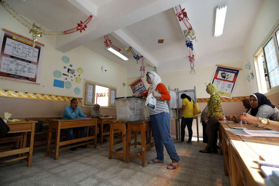 An Egyptian woman casts her vote during the first round of Egyptian parliamentary elections, at a polling station in Alexandria, Egypt, Sunday, Oct. 18, 2015. (AP Photo/Hassan Ammar)