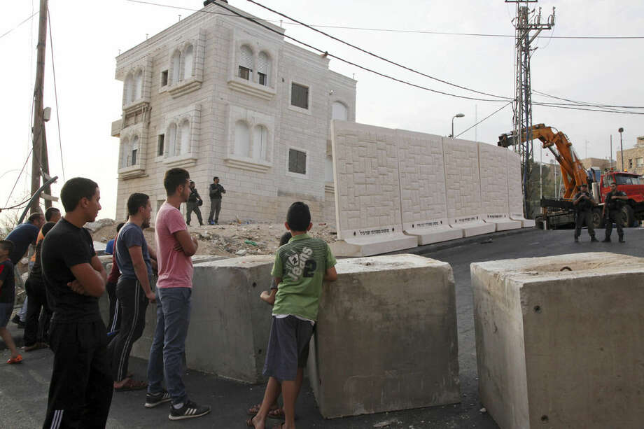 Palestinians watch a wall being built between Palestinian and Jewish neighborhoods in Jerusalem Sunday, Oct. 18, 2015. Palestinians in Jerusalem, more than one-third of the city's population, have awoken to a new reality: Israeli troops are encircling Arab neighborhoods, blocking roads with cement cubes the size of washing machines and ordering some of those leaving on foot to bare their torsos to prove they not carrying knives. (AP Photo/Mahmoud Illean)