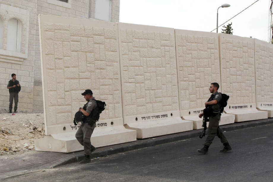 Israeli border policemen walk by the wall being built between Palestinian and Jewish neighborhoods in Jerusalem Sunday, Oct. 18, 2015. Palestinians in Jerusalem, more than one-third of the city's population, have awoken to a new reality: Israeli troops are encircling Arab neighborhoods, blocking roads with cement cubes the size of washing machines and ordering some of those leaving on foot to bare their torsos to prove they not carrying knives. (AP Photo/Mahmoud Illean)