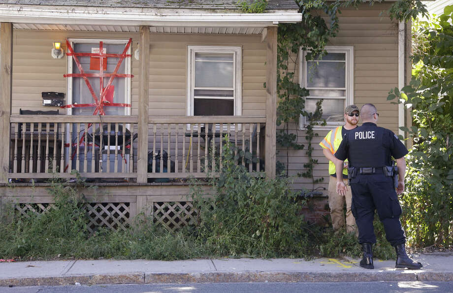 "A Blackstone police officer talks with a utility worker while standing post outside a house where a Massachusetts prosecutor said the bodies of three infants were found Thursday in Blackstone, Mass., Friday, Sept. 12, 2014. Both ""condemned"" and ""keep out"" signs are attached behind police tape to the front door. The utility worker laid some paint markings on the street in front of the house. (AP Photo/Stephan Savoia)"