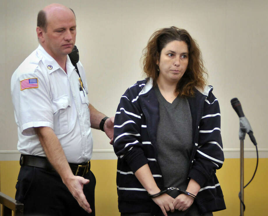 Erika Murray is escorted into the courtroom by a court officer for her arraignment at Uxbridge District Court in Uxbridge, Mass. on Friday, Sept. 12, 2014. Murray, 31, was arrested Thursday night on charges including fetal death concealment, witness intimidation and permitting substantial injury to a child. Not guilty pleas were entered Friday on her behalf. Detectives investigating a case of reckless endangerment of children found the bodies this week at the house littered with soiled diapers in Blackstone, about 50 miles southwest of Boston. (AP Photo/Worcester Telegram & Gazette, Paul Kapteyn, Pool)
