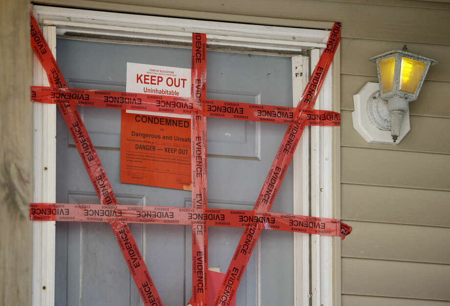 """Both """"condemned"""" and """"keep our"""" signs are attached behind police tape to the front door of a house where a Massachusetts prosecutor said the bodies of three infants were found Thursday in Blackstone, Mass., Friday, Sept. 12, 2014. Erika Murray, 31, was arrested Thursday night on charges including fetal death concealment, witness intimidation and permitting substantial injury to a child. Not guilty pleas were entered Friday on her behalf. (AP Photo/Stephan Savoia)"""