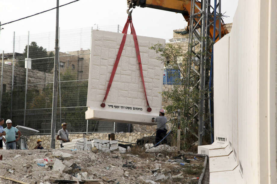 Workers unload a part of the wall being built between Palestinian and Jewish neighborhoods in Jerusalem Sunday, Oct. 18, 2015. Palestinians in Jerusalem, more than one-third of the city's population, have awoken to a new reality: Israeli troops are encircling Arab neighborhoods, blocking roads with cement cubes the size of washing machines and ordering some of those leaving on foot to bare their torsos to prove they not carrying knives. (AP Photo/Mahmoud Illean)