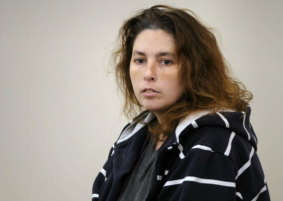 Erika Murray enters the courtroom by a court officer for her arraignment at Uxbridge District Court in Uxbridge, Mass. on Friday, Sept. 12, 2014. Murray, 31, was arrested Thursday night on charges including fetal death concealment, witness intimidation and permitting substantial injury to a child. Not guilty pleas were entered Friday on her behalf. Detectives investigating a case of reckless endangerment of children found the bodies this week at the house littered with soiled diapers in Blackstone, about 50 miles southwest of Boston. (AP Photo/Worcester Telegram & Gazette, Paul Kapteyn, Pool)