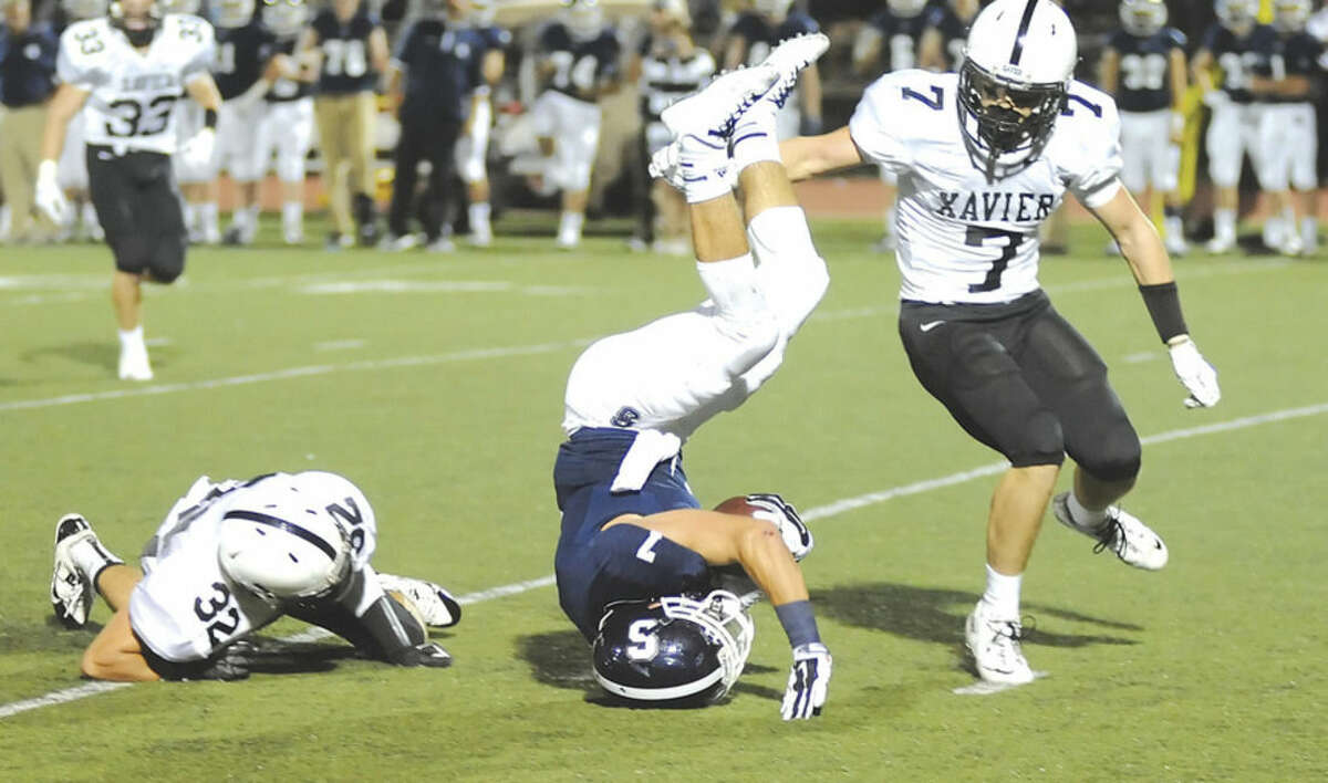 Hour photo/John Nash Staples running back Owen Burke, center, gets upended by Xavier's Edwin Luster (32) as Falcons teammate John Sullivan comes in to finish the job during Friday night's game in Westport. Xavier won on a last second field goal, 3-0.