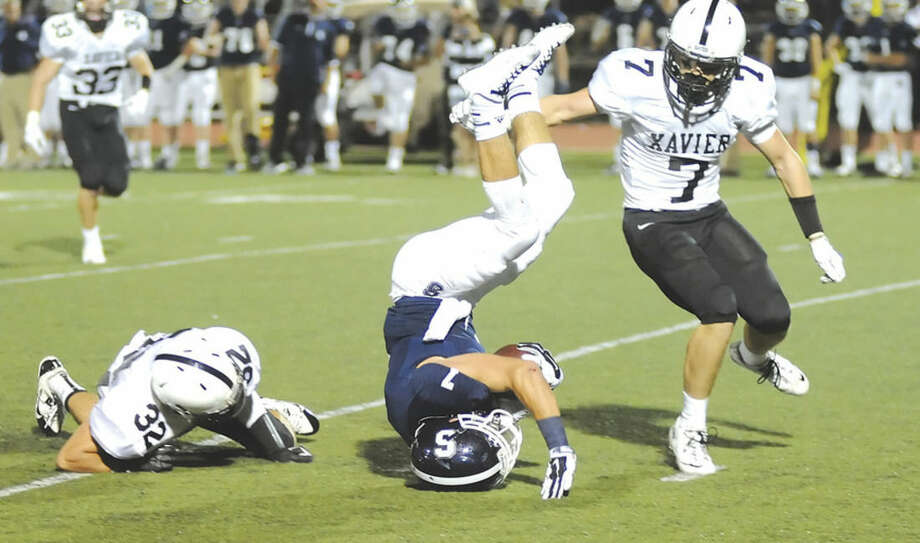 Hour photo/John NashStaples running back Owen Burke, center, gets upended by Xavier's Edwin Luster (32) as Falcons teammate John Sullivan comes in to finish the job during Friday night's game in Westport. Xavier won on a last second field goal, 3-0.