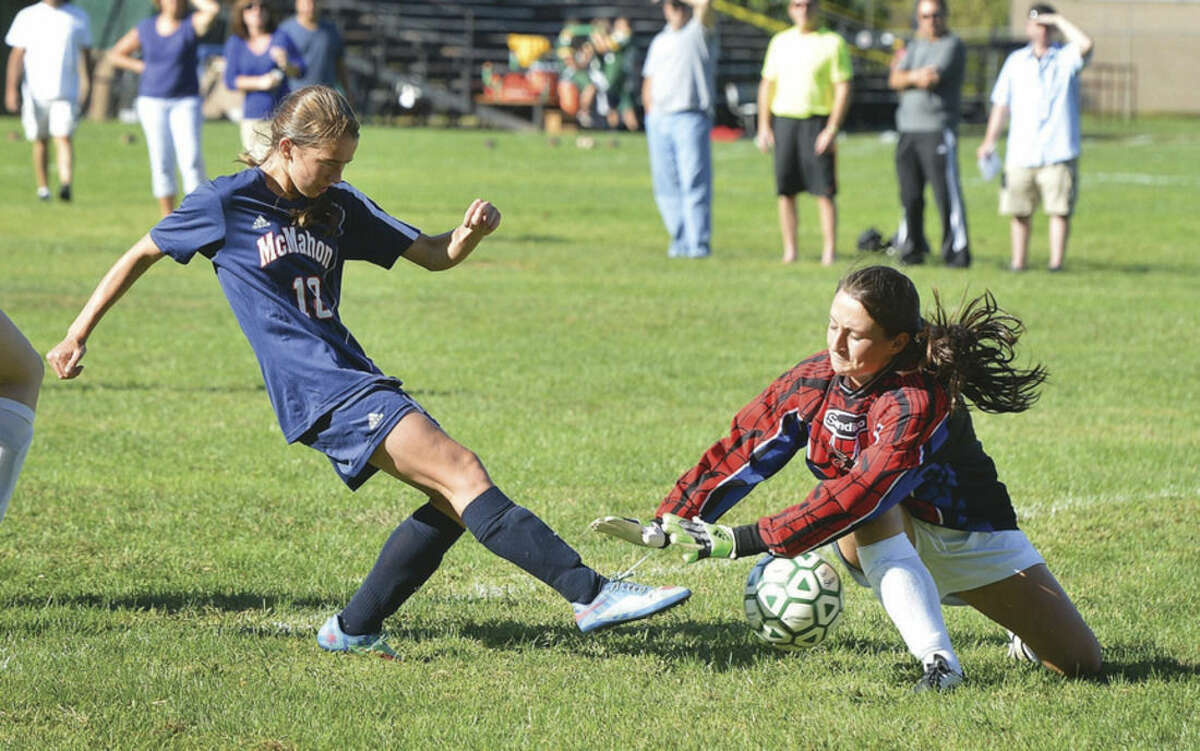 Hour Photo/Alex von Kleydorff McMahon's Marysia Slowik slips a shot past Trinty Catholic goalkeeper and Norwalker Amy Hurd during Friday afternoon's game.