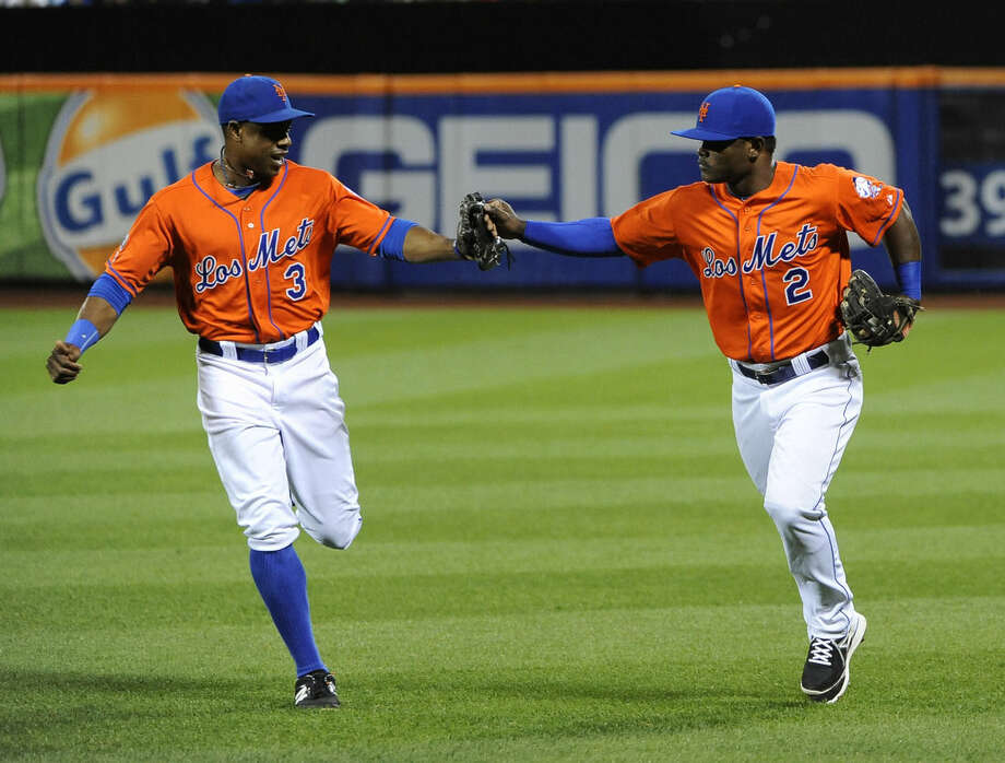New York Mets right fielder Curtis Granderson (3) congratulates second baseman Dilson Herrera (2) after Herrara caught a line drive hit by Washington Nationals' Asdrubal Cabrera for at the third out in the second inning of a baseball game Friday, Sept. 12, 2014, in New York. (AP Photo/Kathy Kmonicek)