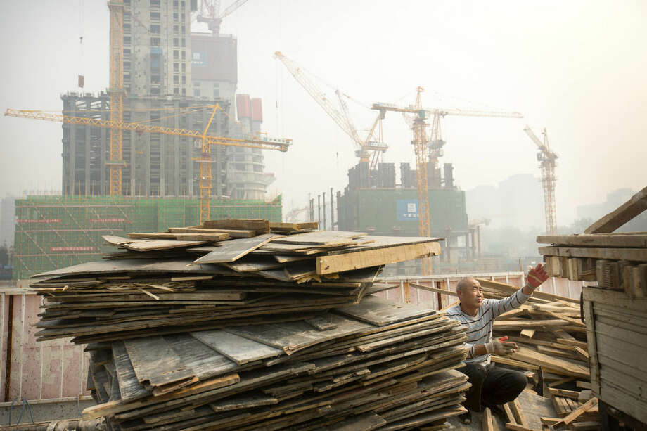 FILE - In this Oct. 6, 2015 file photo, a worker tosses boards onto the back of a truck at a construction site in Beijing. China's economic growth decelerated in the latest quarter but relatively robust spending by Chinese consumers helped to avert a deeper downturn. The world's second-largest economy grew by 6.9 percent in the three months ended in September, the slowest since early 2009 in the aftermath of the global crisis, data showed Monday, Oct. 19, 2015. That was down from the previous quarter's 7 percent. (AP Photo/Mark Schiefelbein, File)