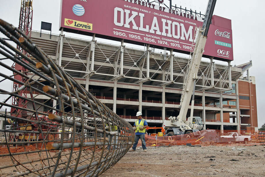 In this Oct. 1, 2015 photo, Jose Bautista works on a rebar support for new footings as renovations continue at the University of Oklahoma's football stadium in Norman, Okla. Tumbling crude prices in oil-rich states are pinching off the largesse that helps universities when state budgets are strained. Oklahoma has scaled back a planned $370 million renovation to its football stadium. (AP Photo/Sue Ogrocki)