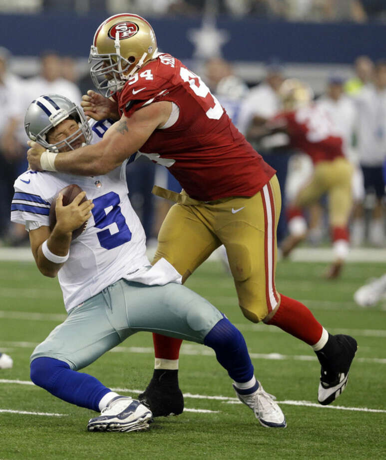 Dallas Cowboys quarterback Tony Romo (9) is sacked by San Francisco 49ers defensive end Justin Smith (94) during the second half of an NFL football game, Sunday, Sept. 7, 2014, in Arlington, Texas. (AP Photo/LM Otero)