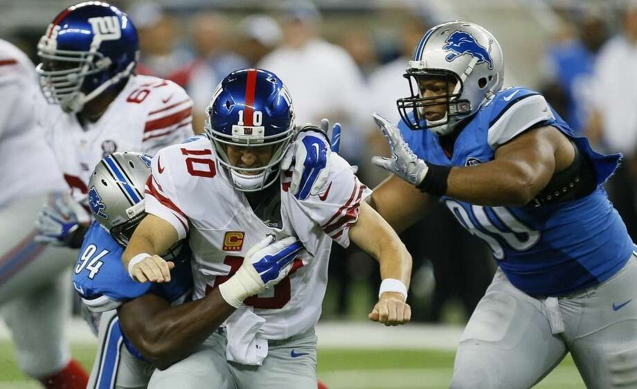 New York Giants quarterback Eli Manning (10) is knocked down by Detroit Lions defensive end Ezekiel Ansah, left, and defensive tackle Ndamukong Suh (90) during the second quarter of an NFL football game in Detroit, Monday, Sept. 8, 2014. (AP Photo/Paul Sancya)