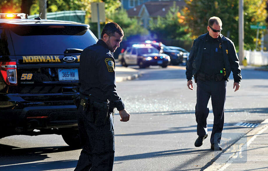 Hour photo / Erik Trautmann Norwalk police investigate a shooting on Ely Ave ooutside Roodner Court Saturday evening.