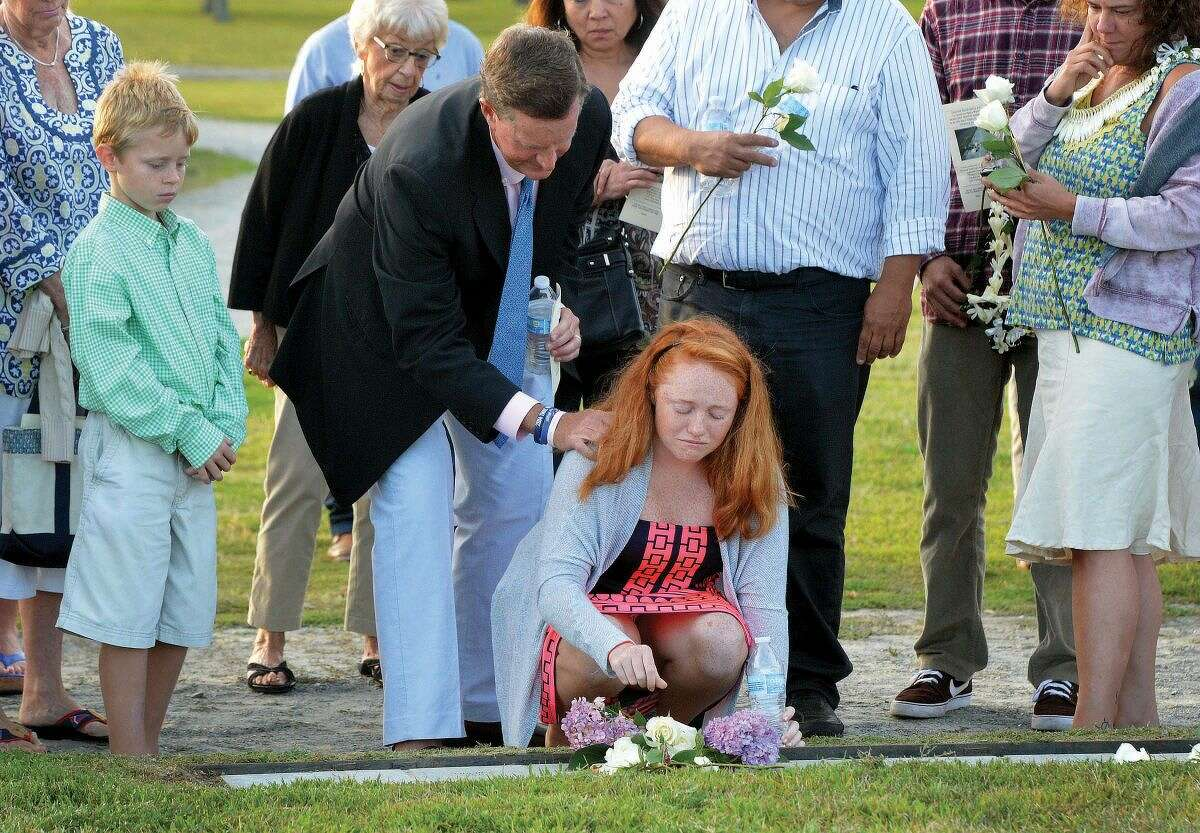 Hour Photo/Alex von Kleydorff. 14 yr old Emma Kathyrn Hunt holds back tears as she places a rose on her father William Christopher Hunt's name with help from family during the Connecticut Remembers September 11th Memorial Ceremony at Sherwood Island state Park, Wednesday evening.