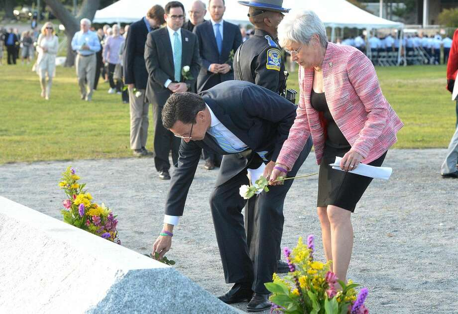 Hour Photo/Alex von Kleydorff. Gov Dannel Malloy and Lt. Gov Nancy Wyman places roses on the marker during the Connecticut Remembers September 11th Memorial Ceremony at Sherwood Island state Park, Wednesday evening