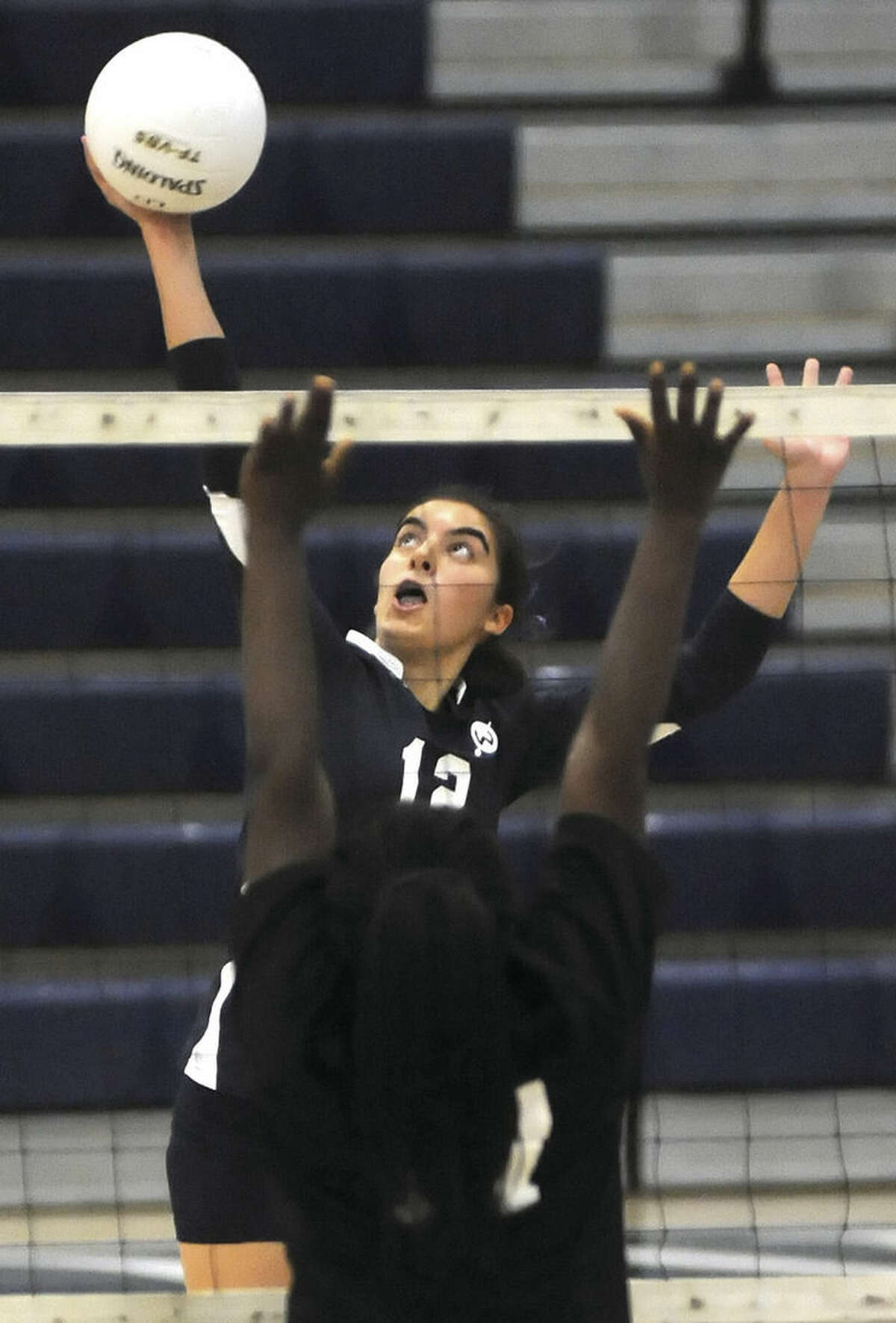 Hour photo/John Nash Wilton's Carly Lovallo, rear, sends down a spike past a Bridgeport Central defender during Wednesday's FCIAC volleyball game at the Zeoli Field House in Wilton.