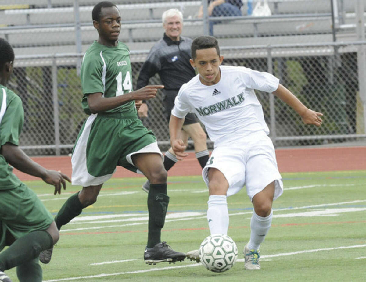 Hour photo/Matthew Vinci Norwalk's Miguel Argueta, right, evades a challenge from Bassick's Todd Mhlange during Tuesday's game.