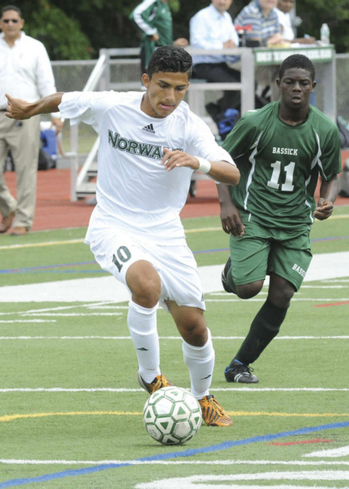 Hour photo/Matthew Vinci Norwalk's Patrick Barrantes, front, dribbles past Bassick's Simon McIntyre during Tuesday's game at Norwalk High. Barrantes scored three first half goals to help the Bears to their first win of the season.