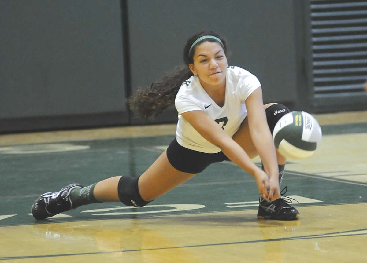 Hour photo/John Nash Norwalk libero Gabriela Davila gets low to try and dig a ball off the court during Wednesday's game against New Canaan at Scarso Gym in Norwalk.