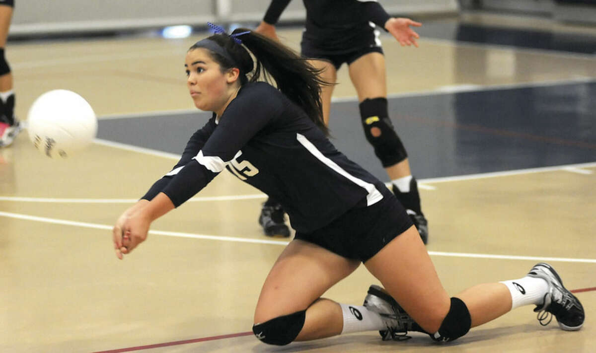 Hour photo/John Nash Wilton's Mary Jane LaSala slides to the court to play the ball during Wednesday's game against Bridgeport Central at the Zeoli Field House in Wilton.