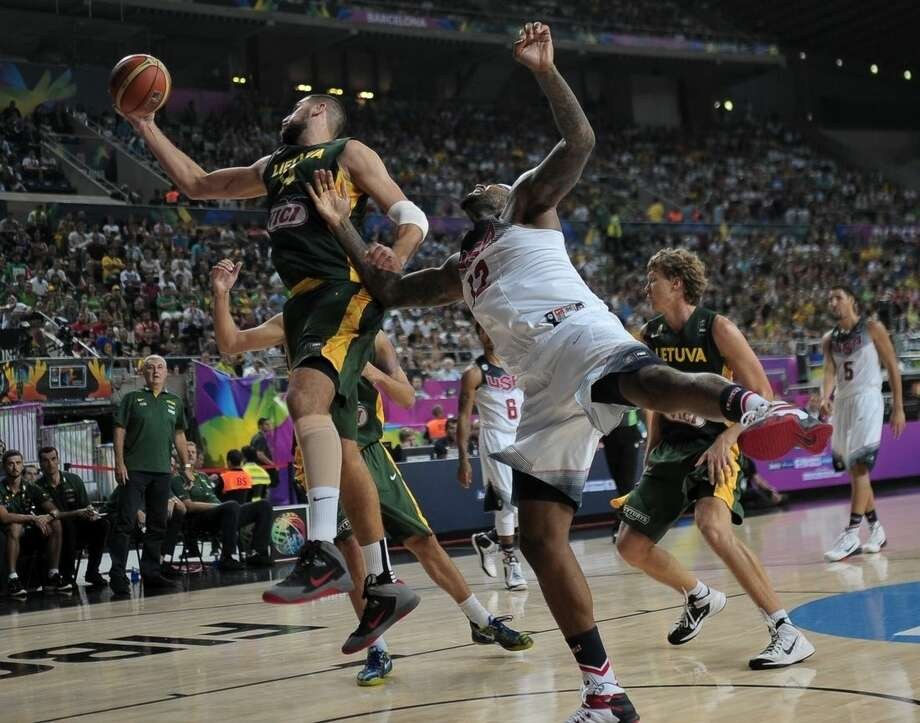 United States's DeMarcus Cousins, right, and Lithuania's Jonas Valanciunas go for the ball during their Basketball World Cup semifinal match at the Palau Sant Jordi in Barcelona, Spain, Thursday, Sept. 11, 2014. The 2014 Basketball World Cup competition will take place in various cities in Spain from Aug. 30 through Sept. 14. (AP Photo/Manu Fernandez)