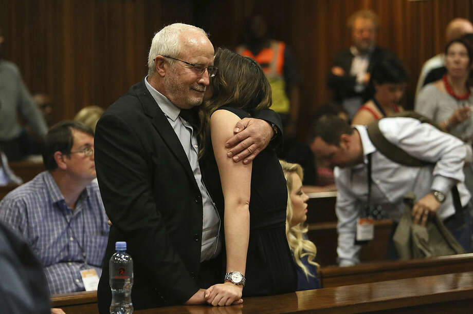 Estranged Father and sister of Oscar Pistorius, Henke Pistorius, left, and Aimee Pistorius, right, embrace one another in court in Pretoria, South Africa, Friday, Sept. 12, 2014. In passing judgement judge Thokozile Masipa ruled out a murder conviction for the double-amputee Olympian in the shooting death of his girlfriend, Reeva Steenkamp, but said he was negligent and convicted him of culpable homicide. (AP Photo/Alon Skuy, Pool)