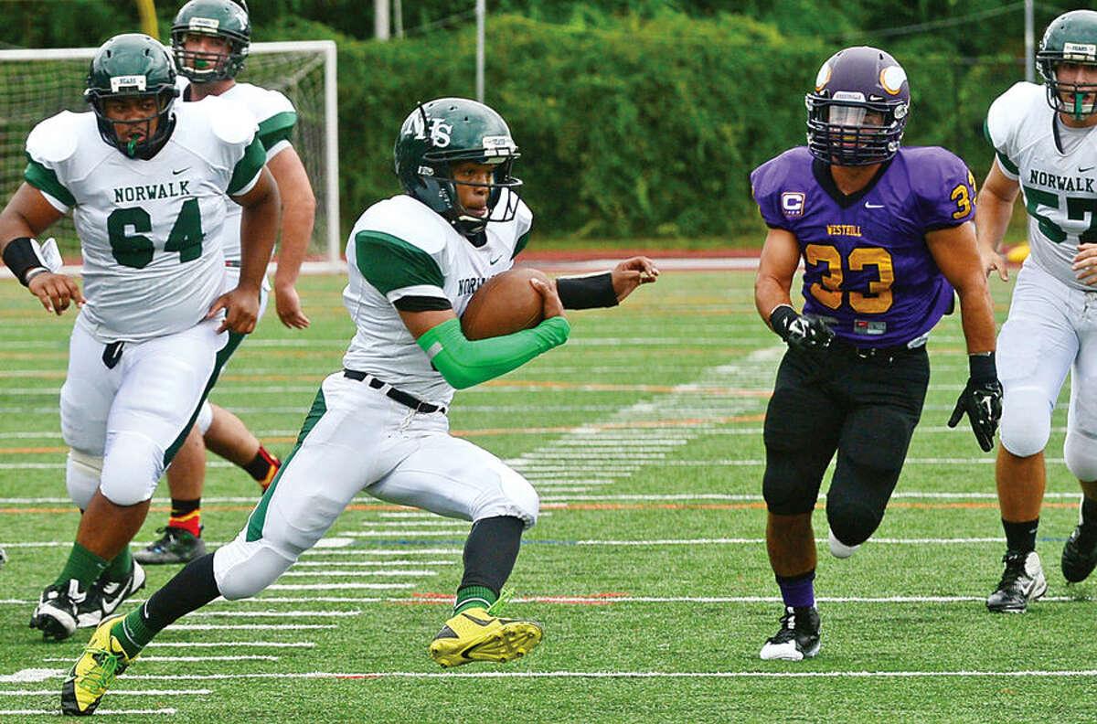 Hour photo / Erik Trautmann Norwalk High School quarterback Jeremy Hinton cuts back around the Westhill defense to score during their game in Stamford Saturday.