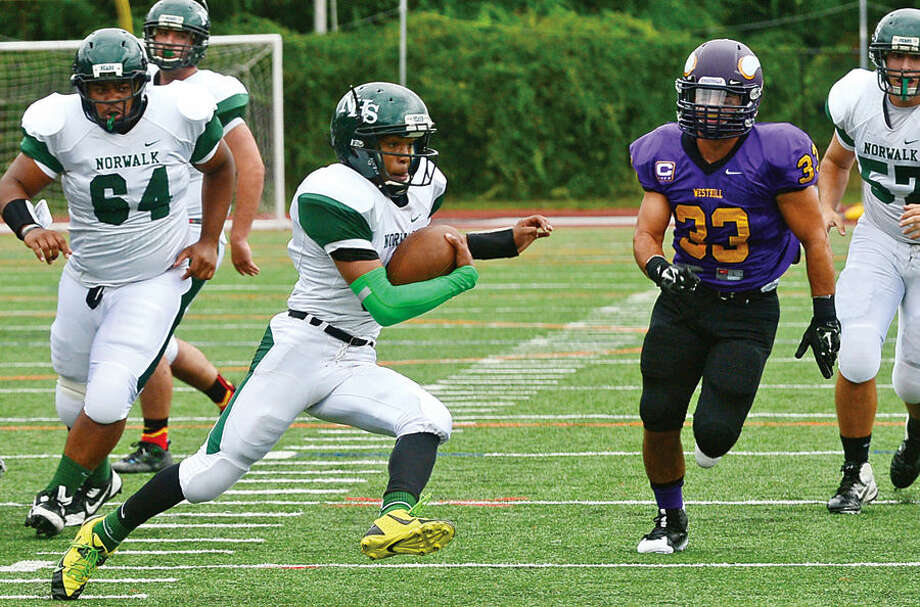 Hour photo / Erik Trautmann Norwalk High School quarterback Jeremy Hinton cuts back around the Westhill defense to score during their game in Stamford Saturday.
