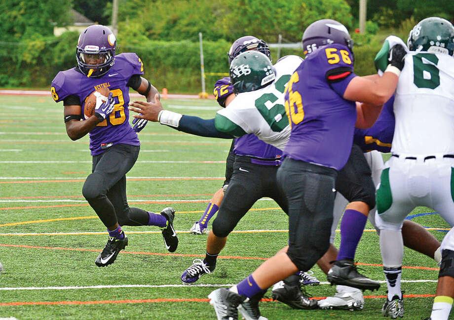 Hour photo / Erik Trautmann Westhill High school's Josh Exantus runs around Norwalk defenders for a touchdown during their game in Stamford Saturday.