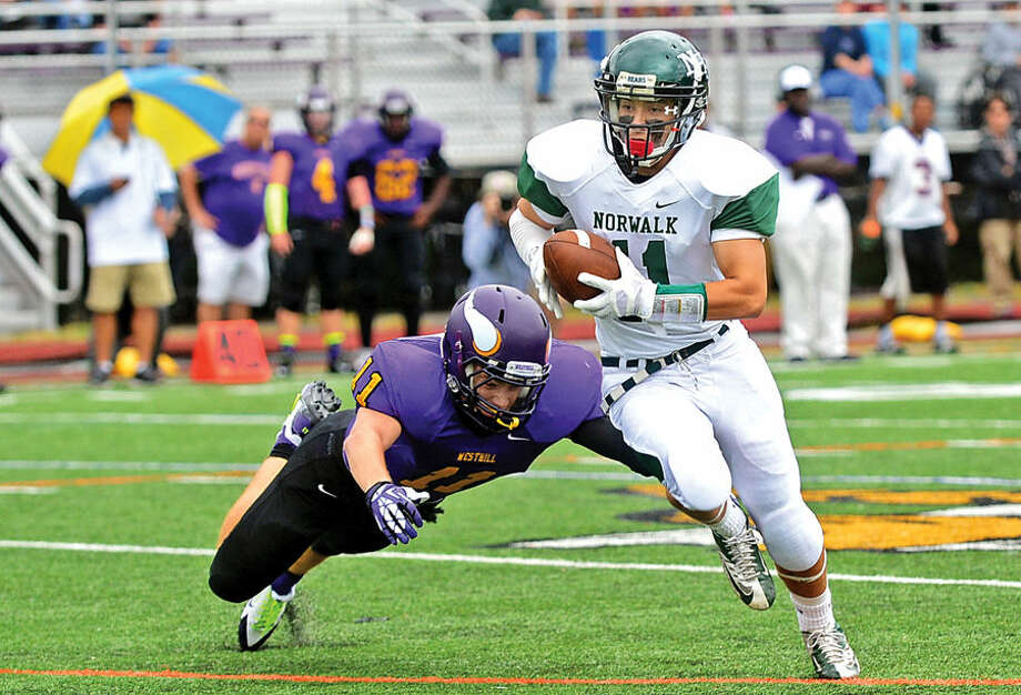 Hour photo / Erik Trautmann Norwalk High School's #11 Yesid Rodriguez advances the ball after a reception during their game against Westhill in Stamford Saturday.
