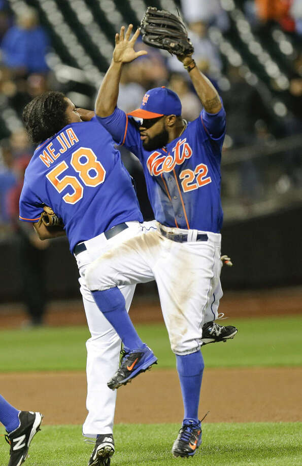 New York Mets' Eric Young Jr. (22) and Jenrry Mejia (58) celebrate after the Mets' 2-0 win over the Colorado Rockies in a baseball game Wednesday, Sept. 10, 2014, in New York. (AP Photo/Frank Franklin II)