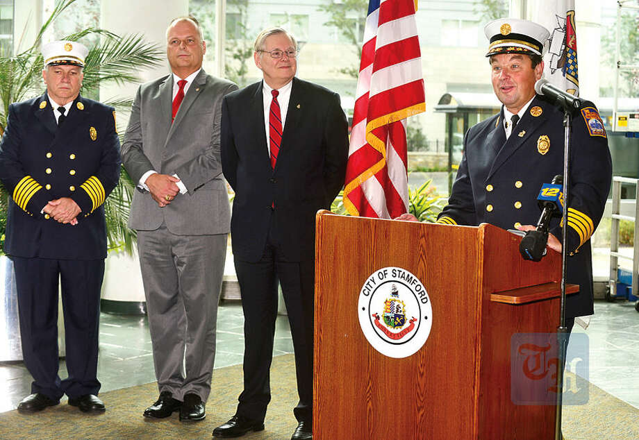 Hour photo / Erik Trautmann Assistant Fire Chief, Trevor Roach, speaks while Director of Public Safety, Ted Jankowski, and Mayor David Martin, look on, during a press conference at the Stamford Government Center Wednesday announcing his appointment to Chief of the Stamford Fire Department after the retirement of Chief Peter Brown, left, in December.