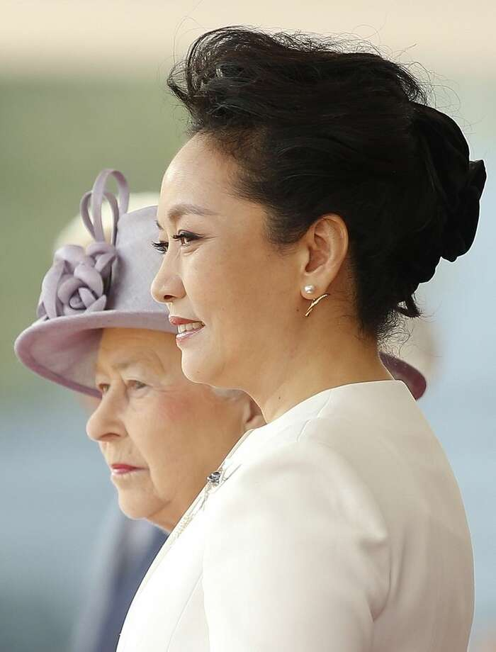 Britain's Queen Elizabeth II, left , and the Chinese First Lady Peng Liyuan watch as Chinese President Xi Jinping inspects a guard of honour during the official welcome ceremony at Horseguards Parade in London, Tuesday, Oct. 20, 2015. Chinese President Xi Jinping arrived in Britain Monday for a four-day state visit as part of a push to increase trade ties between the two countries. (AP Photo/Alastair Grant, Pool)