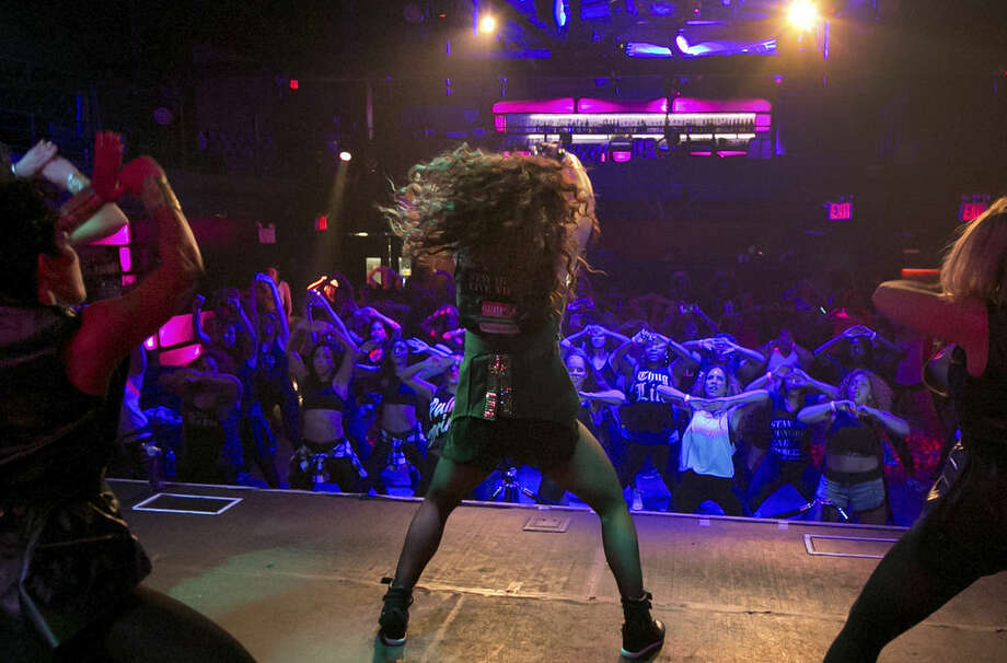 Janet Jones, center, leads a Vixen Workout fitness concert, at the Highline Ballroom, in New York, Saturday, July 26, 2014. Former Miami Heat dancer Janet Jones created the Vixen Workout two years ago after she lost her job as a financial assistant and her high-energy routine has caught on in New York and other cities. (AP Photo/Richard Drew)