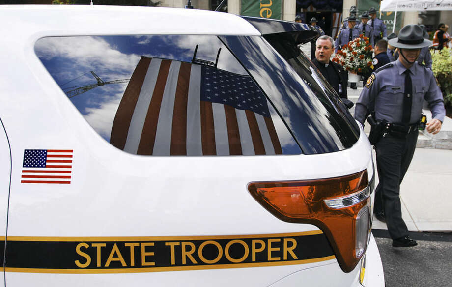 The US flag is reflected in the window of a Pennsylvania State Police vehicle in front of the Rotunda at Marywood University on Wednesday, Sept. 17, 2014 in Scranton, Pa., for the viewing of Pennsylvania State Trooper Cpl. Bryon Dickson. Dickson was killed on Friday night in an ambush shooting at the state police barracks in Blooming Grove Township. Authorities are looking for 31-year-old Eric Frein, of Canadensis, who is charged with killing one trooper and wounding another outside the barracks. (AP Photo/The Scranton Times-Tribune, Butch Comegys) WILKES BARRE TIMES-LEADER OUT; MANDATORY CREDIT