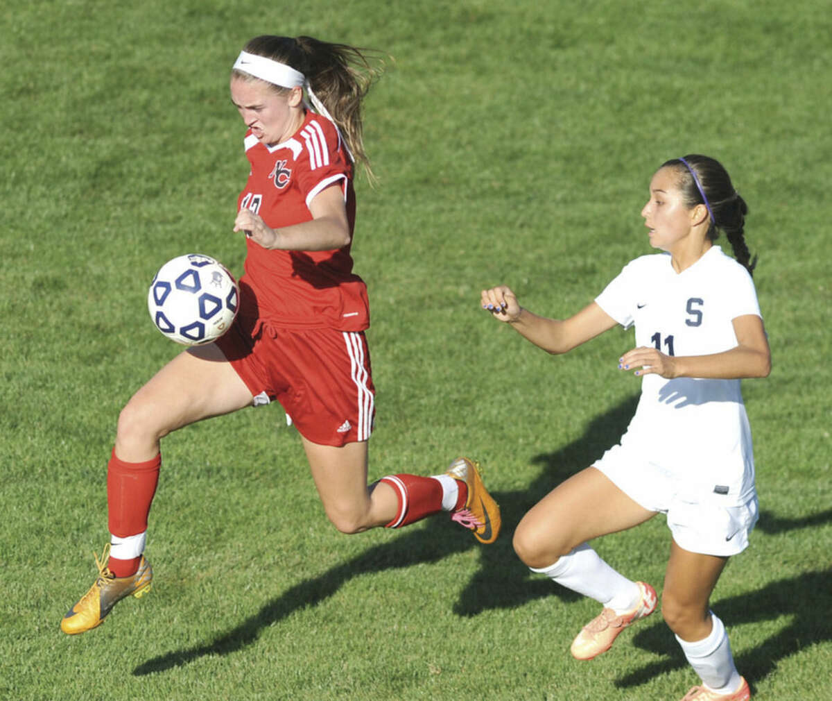 Hour photo/John Nash New Canaan's Samantha Stewart plays the ball in front of Staples' Tia Zajec during Wednesday's FCIAC girls soccer game at Loeffler Field in Westport. The Rams and Wreckers tied 1-1.