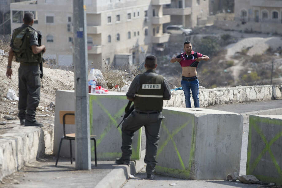 Israeli border policemen order a Palestinian man to lift his shirt at a checkpoint before is allowed to exit the Arab neighborhood of Issawiyeh in Jerusalem, Tuesday, Oct. 20, 2015. U.N. Secretary-General Ban Ki-moon will make a surprise visit to Israel and the Palestinian territories on Tuesday, in a high-profile gambit to bring an end to the monthlong wave of violence that has plagued the region. (AP Photo/Ariel Schalit)