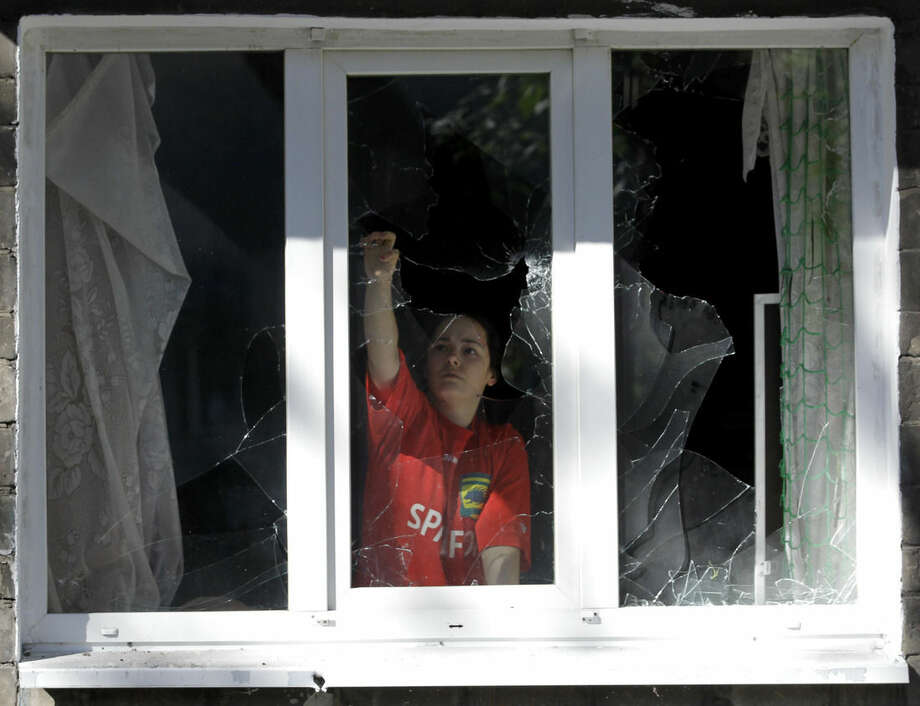 A girl clears the broken glass at a damaged apartment building after shelling in the town of Donetsk, eastern Ukraine, Wednesday, Sept. 17, 2014. Ukraine moved to resolve months of crisis Tuesday by strengthening ties to Europe and loosening some controls over the country's rebellious eastern regions where it has been fighting Russian-backed separatists. (AP Photo/Darko Vojinovic)