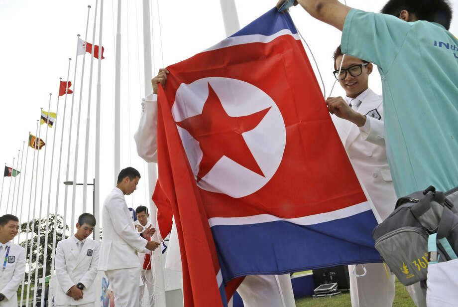 Flag bearers practice to hoist a North Korean flag during a team welcoming ceremony at the 17th Asian Games in Incheon, South Korea, Thursday, Sept. 18, 2014. (AP Photo/Dita Alangkara)