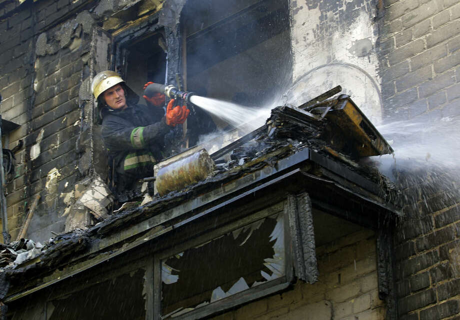A firefighter sprays water at damaged apartment building after shelling in the town of Donetsk, eastern Ukraine, Wednesday, Sept. 17, 2014. Ukraine moved to resolve months of crisis Tuesday by strengthening ties to Europe and loosening some controls over the country's rebellious eastern regions where it has been fighting Russian-backed separatists. (AP Photo/Darko Vojinovic)