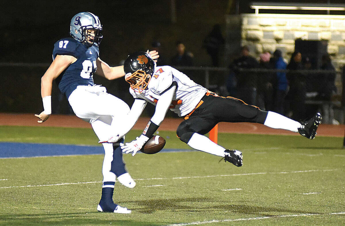 Hour photo/John Nash - Staples punter Ryan Fitton, left, has hit kick blocked by Ridgefield's Dante Cobelli during the first quarter of Friday night's FCIAC football game in Westport. Ridgefield turned the short field into a touchdown en route to a 31-27 win over the previously undefeated Wreckers.