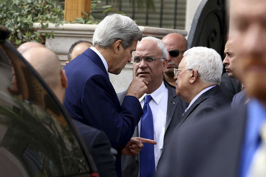 U.S. Secretary of State John Kerry, center left speaks with Palestinian President Mahmoud Abbas center right, and close aide to Abbas, Saeb Erekat, center, after their meeting at Abbas' residence in Amman, Jordan, Saturday, Oct. 24, 2015. Kerry said Saturday that Israel and Jordan have agreed on steps aimed at reducing tensions at a holy site in Jerusalem that have fanned Israeli-Palestinian violence. (AP Photo/Raad Adayleh)