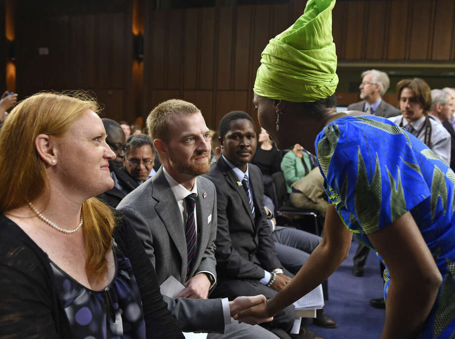 Ebola survivor Dr. Kent Brantly, former Medical Director of Samaritan's Purse Ebola Care Center in Monrovia, Liberia, center, talks with Emira Woods, right, Director of Social Impact at ThoughtWorks, right, before the start of a hearing on Ebola before the Senate Appropriations Subcommittee on Labor, Health and Human Services, and Education on Capitol Hill in Washington, Tuesday, Sept. 16, 2014. Brantly's wife Amber watches at left. Woods thanked Brantly for his work fighting Ebola in Liberia. (AP Photo/Susan Walsh)
