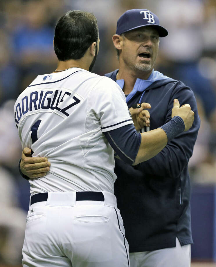 Tampa Bay Rays hitting coach Derek Shelton, right, holds back Sean Rodriguez after both the Rays and New York Yankees benches emptied during the eighth inning of a baseball game Tuesday, Sept. 16, 2014, in St. Petersburg, Fla. Tempers flared when Rays pitcher Steven Geltz hit Derek Jeter with a pitch. (AP Photo/Chris O'Meara)