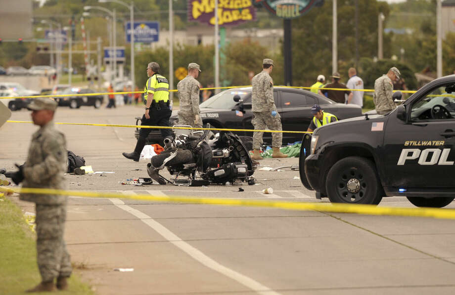 A damaged police motorcycle rests in the intersection after a vehicle crashed into a crowd of spectators during the Oklahoma State University homecoming parade, causing multiple injuries, on Saturday, Oct. 24, 2015 in Stillwater, Oka.(AP Photo/Brody Schmidt)
